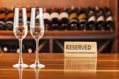 Två exponeringsglas med champagne i bakgrund med flaskor av vin Royaltyfri Fotografi