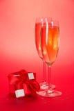 Två exponeringsglas med champagne och den lilla gåvaasken royaltyfri foto