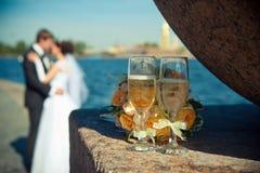 Två exponeringsglas med champagne och en bukett av rosor på en backgroun Arkivbild
