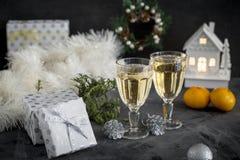 Två exponeringsglas med champagne och mandariner och gåvor på svart bakgrund arkivbild