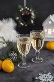Två exponeringsglas med champagne och mandariner på svart bakgrund royaltyfria foton