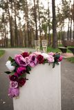 Två exponeringsglas med champagne står på en sockel som dekoreras med blommor arkivbilder