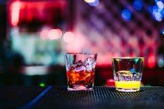 Två exponeringsglas med coctailar på en kugge av stången i nattklubb royaltyfri bild