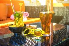 Två exponeringsglas med fruktsaft och plattan med muttrar och chiper, gul solglasögon i förgrunden på en tabell i det friakafé på royaltyfri foto
