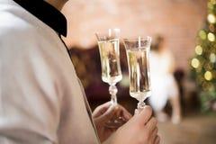 Två exponeringsglas med mousserande vin i manligt arkivfoton