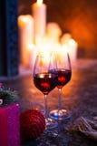Två exponeringsglas med rött vin på julgran- och spisbackgrou Arkivfoto