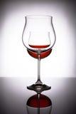 Två exponeringsglas med rött vin som skapar illusionen av tre Arkivbild