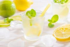 Två exponeringsglas med sommardrinkmojito med limefrukt, citronen och mintkaramellen, med iskuber på vit träbakgrund arkivfoton