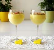 Två exponeringsglas med vaniljkräm dekorerade med kulöra stänk royaltyfria foton