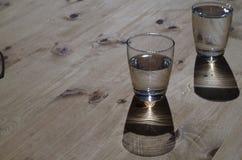 Två exponeringsglas med vatten på en trätabell Royaltyfri Fotografi