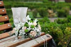 Två exponeringsglas och bröllopbukett på en bänk Royaltyfri Foto