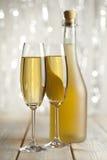 Två exponeringsglas och flaska av champagne royaltyfria bilder