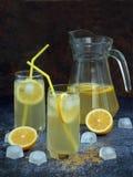 Två exponeringsglas och kanna av kall hemlagad lemonad med citronskivor, iskuber, farin, gula sugrör Royaltyfri Fotografi