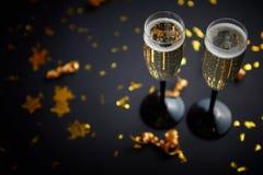 Två exponeringsglas som är fulla av att moussera champagnevin med guld- garnering arkivfoto