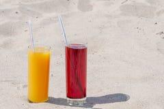Två exponeringsglasexponeringsglas med fruktsaft av mango och körsbäret med tubules Sandy Beach p? en sommardag arkivfoto