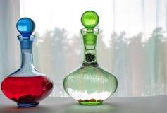 Två exponeringsglaskaraffer med frukt- och bärdrinkar royaltyfri foto