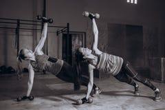 Två färdiga kvinnor i idrottshallen som gör kondition, övar med hantlar som blir i planka, poserar, svartvitt Royaltyfri Foto