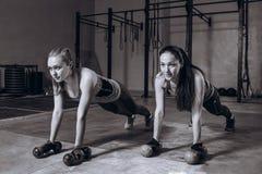 Två färdiga kvinnor i idrottshallen som gör kondition, övar med hantlar som blir i planka, poserar, svartvitt Fotografering för Bildbyråer