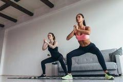 Två färdiga kvinnor som gör genomköraresporten och kondition för squats den hemmastadda kvinnliga royaltyfri bild