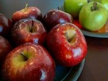 Två färgade äpplen - som är gröna och som är röda på blått och orange keramisk pl Arkivbild