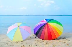 Två färgglade paraplyer på stranden Arkivbilder