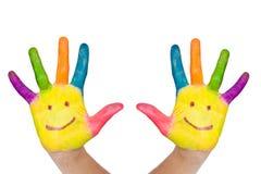 Två färgrika händer med leende Arkivfoto