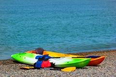 Två färgrika havskajaker med skovlar och flytvästar på den steniga stranden royaltyfri fotografi