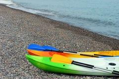 Två färgrika havskajaker med skovlar på den steniga stranden royaltyfri foto