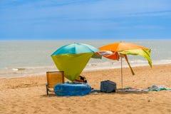 Två färgrika solparsols och en stol på en blåsig solig strand Arkivbild