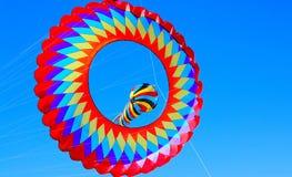 Två färgrika stora drakar som flyger i klar blå himmel Fotografering för Bildbyråer