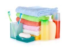 Två färgrika tandborstar, skönhetsmedelflaskor, tvål och handdukar Royaltyfri Bild