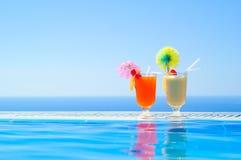 Två färgrika tropiska coctailar nära simbassängen på bakgrund av det varma blåa havet Exotisk sommarsemester Arkivbild
