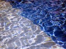 Två färgtoner av vatten i en simbassäng Arkivfoton