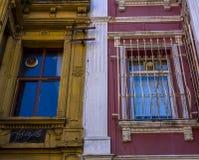 Två fönster i de angränsande byggnaderna Windows på den orange och rosa väggen Galler på fönstren arkivfoton