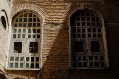 Två fönster i skugga och ljus på tegelplattategelstenväggen royaltyfri bild