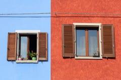 Två fönster med slutare på den färgrika väggen Arkivfoto