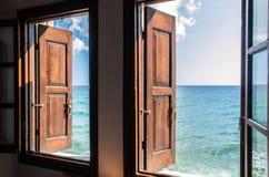 Två fönster med träbruna slutare öppnar att förbluffa sikt på det ändlösa havet för akvamarin och blå himmel, inga personer omkri royaltyfri fotografi
