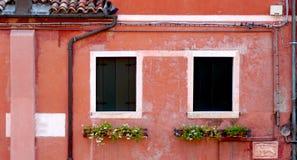 Två fönster och tömt rör med korallfärgväggen royaltyfria foton