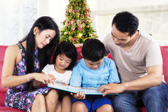 Två föräldrar hjälper deras barn att läsa Arkivbilder
