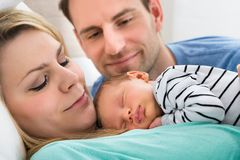 Två föräldrar som ser, behandla som ett barn Royaltyfria Foton