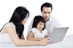Två föräldrar som undervisar deras dotter med bärbara datorn Fotografering för Bildbyråer