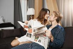 Två förälskade gulliga europeiska personer och att kyssa och krama, medan sitta på soffan hemma och att läsa tidningen i pyjamas royaltyfria foton