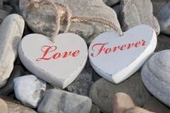 Två förälskelsehjärtor på en stenig strand som en Arkivfoton
