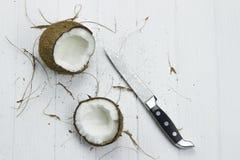 Två för kokosnötkokosnöt för kokosnöt skräp- nya tropiska bruna vita organiska flingor mjölkar kniven på trävit bakgrund Fotografering för Bildbyråer