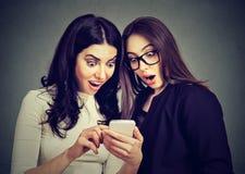 Två förbluffade kvinnarumskamrater som håller ögonen på erbjudanden på linje på en smart telefon royaltyfri fotografi