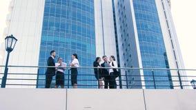 Två företag av coworkers som står på terrass och diskuterar resultaten av deras forskningar arkivfilmer