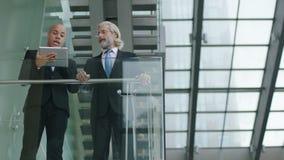 Två företags ledare som diskuterar affär genom att använda den digitala minnestavlan lager videofilmer