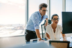Två företags professionell som tillsammans arbetar på datoren arkivfoton