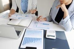 Två företagsledarekvinnor som diskuterar diagrammen och graferna som visar resultaten arkivbilder