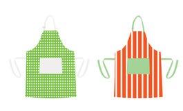Två förkläden med kökmodeller Arkivfoton